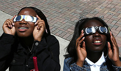 On the first day of school, 11th grade students and sisters Stephanie Byrd, 16, and Danyel Rolle, 15, right, gaze toward the sky on Monday, Aug. 21, 2017 to witness the partial eclipse at Booker T. Washington Senior High School in Miami, Fla. Photo by Carl Juste/Miami Herald/TNS/ABACAPRESS.COM