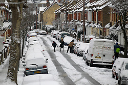 © Licensed to London News Pictures. 21/01/2013, London, UK. People walk across a snow covered street in Croydon, South London, Monday, Jan. 21, 2013. Britain is continue affect by cold weather and snow. Photo credit : Sang Tan/LNP