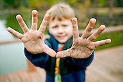 A boy holds up his dirty hands