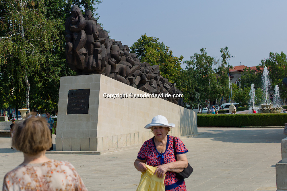 Moldova Chisinau woman at fleamarket in front of monument rmemebering the victims of communism