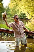 A paddler poses for a portrait by the Olentangy River in central Ohio.  His handmade wooden canoe is seen behind him.