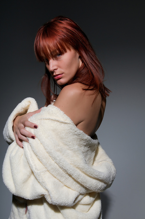 Young caucasican redhair woman, posing sensual with robe.
