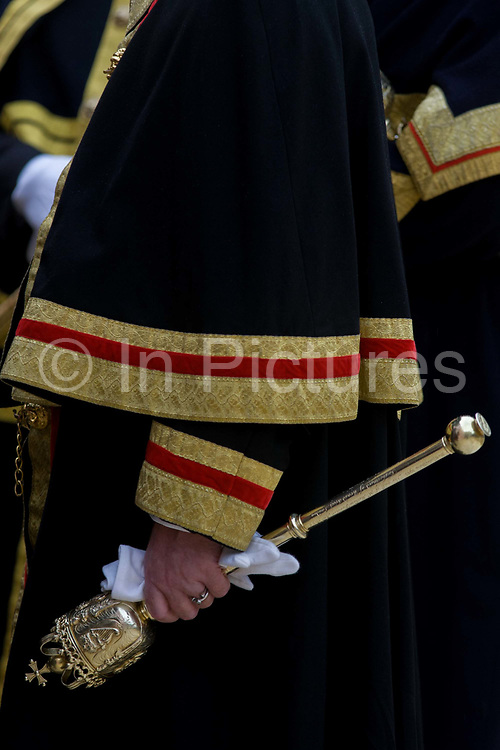 """A Beadle mace-bearer from the City of London holds a ceremonial mace in the crook of his left arm during the annual Lord""""s Mayor's Show. We see only the arm and the golden mace as a close-up detail. The Beadle's role is now only symbolic, accompanying the City Adlermen as the lead the processions through the capital's ancient financial heart. A Beadle or bedel was a lay official of a church or synagogue who would usher, keep order, make reports, and assist in religious functions; or a minor official who carries out various civil, educational, or ceremonial duties. The term has Franco-English pre-renaissance origins, derived from the Vulgar Latin """"bidellus"""" or """"bedellus"""", rooted in words for """"herald"""". It moved into Old English as a title given to an Anglo-Saxon officer who summoned householders to council."""