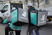 Two Deliveroo cycle couriers with their large back boxes while out delivering in London, England, United Kingdom.