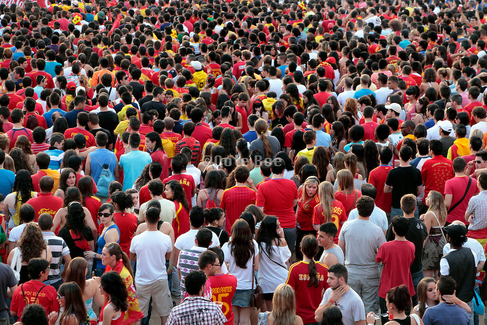 crowd of people standing watching a sports game on a big screen Spain