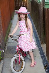 Little girl standing by her bike,