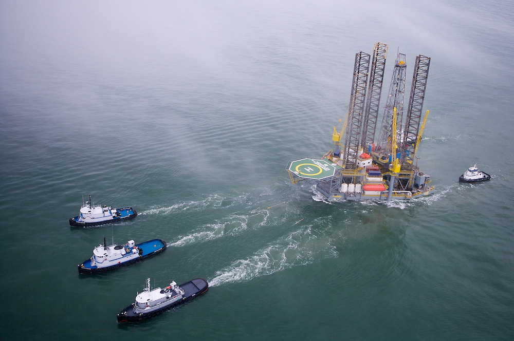 Jackup offshore oil drilling rig in the Gulf of Mexico being towed to new location by 4 tugboats.