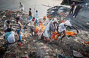 EXCLUSIVE<br /> Where funeral fires forever burn: Incredible photos show the 'Manikarnika Ghats' holy festival on the Ganges where Hindus make their final journey find 'moksha' and reach nirvana<br /> <br /> On the western bank of the Ganges in the ancient city of Varanasi, the fires of the Manikarnika Ghats have been burning for thousands of years.<br /> This holy city, in Uttar Pradesh, India, is the most sacred place on earth for Hindus and it is believed that if a person's ashes are scattered here then their soul will finally achieve nirvana (moksha). <br /> But to liberate the soul, the worn-out body must first be burned. <br /> A series of stunning and rare images, captured by photographer Michal Huniewicz, give a remarkable insight into the last hours of the Hindu body at Manikarnika Ghats - the largest cremation site in Varanasi.<br /> <br /> Up to 300 people a day are cremated at this 'burning ghat', named for the steps that lead down to a body of holy water.<br /> For centuries, the old and sick have flocked to the site to die here on the banks of the Ganges, and special buildings on the site are reserved for those awaiting their final hours.<br /> But the atmosphere at the giant funeral site is not one of sorrow, as mourners instead laugh, chat and play cards as the funeral preparations are carried out.<br /> The Hindu attitude to death is not one of loss, but instead follows the idea of 'shedding' the worn-out body, as one might throw away clothes that are too worn-out to wear.<br /> The Varanasi site is a hive of activity, families weave between the piles of wood gathered for burning bodies; livestock amble around funeral parties; and spectators and tourists mill around observing ceremonies.<br /> The funeral process is vital in achieving nirvana, and the ritual's many stages must be perfectly performed or the soul won't find its way in the afterlife. <br /> <br /> To begin, the remains are carried through the alleyways of the old city to the holy Ganges on a bamboo stretcher swathed in colourful cloth. <br /> The closest male relati