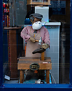 A mannequin in the window of a shoe repair shop wears a mask during the covid-19 pandemic on the high street of Cheltenham, England on 22nd November, 2020.