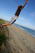 Jumping off a dune at Martha's Vineyard, Massachusetts. MODEL RELEASED..