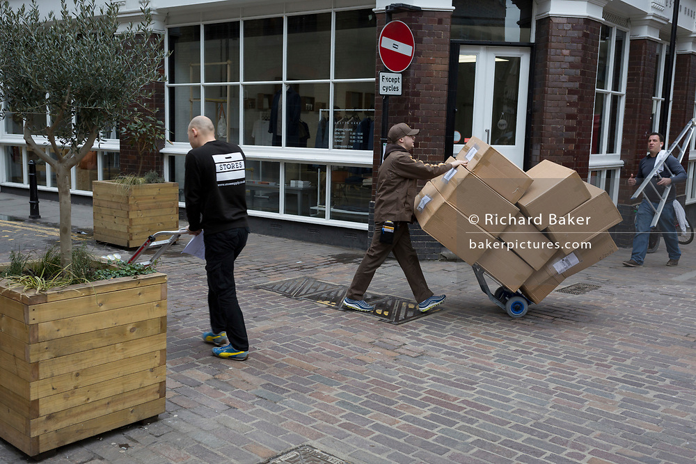 A UPS courier pushes a pile of boxes on a trolley to a nearby address in Shoreditch, 7th March 2018, in east London England.
