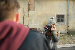 Teenage girl taking picture of her boyfriend with retro styled camera, Munich, Bavaria, Germany