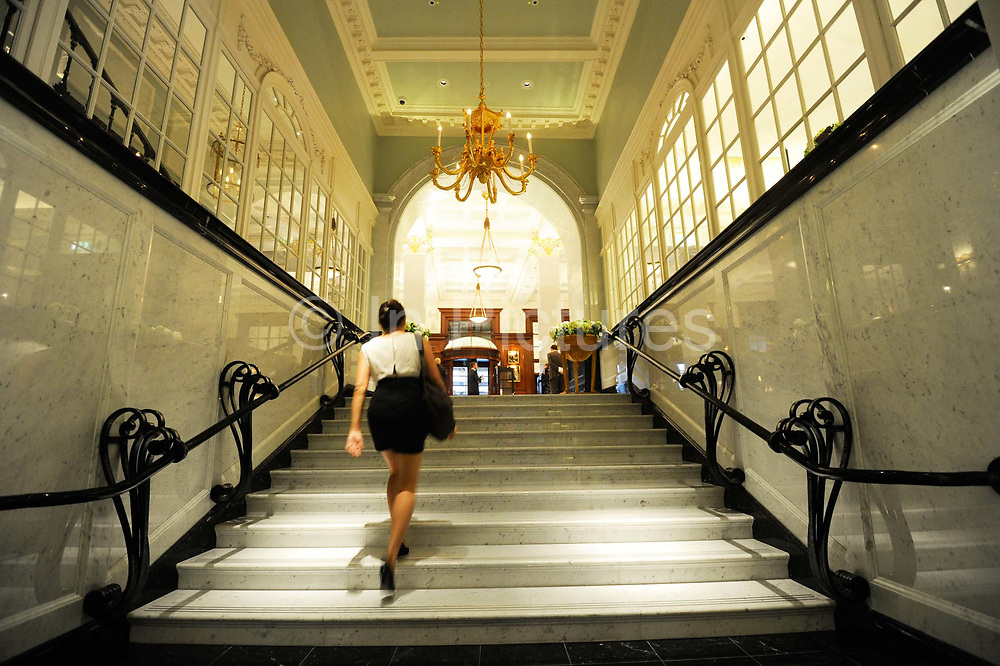 """A woman walks up a stairway leading to the front hall reception of the Savoy Hotel in London. The iconic hotel reopened after a three year refit that cost £220 million ($350 million). The Savoy Hotel is a located on the Strand, in central London. Built by impresario Richard D'Oyly Carte the hotel opened on 6 August 1889. It was the first in the Savoy group of hotels and restaurants owned by Carte's family for over a century. It has been called """"London's most famous hotel"""" and remains one of London's most prestigious and opulent hotels, with 268 rooms and panoramic views of London."""