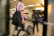 airport people with there luggage walking through a sliding door towards the passenger terminal