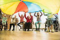 Girls and senior women doing gentle sports exercise with parachute in rest home