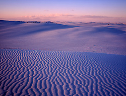 Dusk at White Sands Nat. Monument looking across a field of white gypsum sand tinted blue and rose by twilight