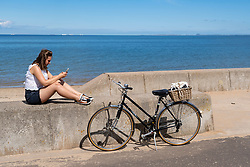 Portobello, Scotland, UK. 8 May 2020. Images from Friday afternoon during Covid-19 lockdown on promenade at Portobello. Promenade and beach were busier than in recent weeks due to warm sunny weather and the fact that several cafes and takeaway food shops are now open. Police patrols were low key. Pictured; Woman relaxes in sunshine on sea wall. Iain Masterton/Alamy Live News
