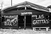 VISTA DE LA ENTRADA A UNO DE LOS TANTOS BURDELES EN LA ZONA DE MINERIA ILEGAL DE LA PAMPA. EL IMPACTO DE LA MINERIA ILEGAL EN EL PERU ES DE MAS DE 40,000 HECTAREAS DE BOSQUES DESTRUIDOS. <br /> LA CANTIDAD DE ORO ILEGALMENTE EXTRAIDO EN EL PERU, SUPERA LOS 1,300 MILLONES DE DOLARES AL AÑO. ESTA ACTIVIDAD PRODUCE IMPACTOS NEGATIVOS A CUENCAS HIDROGRAFICAS ENTERAS Y MUCHOS DE LOS CASOS DE MANERA IRREMEDIABLE.