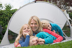 Mother with young kids small tent garden lawn
