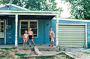 Four young children half-dressed and in their underwear standing on the porch of a rundown house in Naples, Illinois