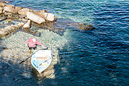 A man starts his motor on his dinghy fo an afternoon on the sea.