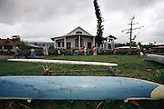 Villagers clean up the outside of the Poutasi Village church, Western Samoa on White Sunday. White Sunday (also called Children's Day) is celebrated on the second Sunday of October each year. In this tradition brought to the island by the London Missionary Society, the children receive new clothes and gifts, and festive games are played. Most attend church services and then gather for family feasts that feature foods like pork, taro, and coconuts. Western Samoa. Material World Project.