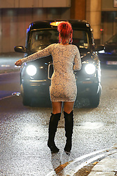© Licensed to London News Pictures . 01/01/2014 . Manchester , UK . A woman stands in the middle of the road and flags down a taxi . Revellers see in the New Year in Manchester today (January 1st 2014) as police report that officers are at full stretch responding to calls . Photo credit : Joel Goodman/LNP
