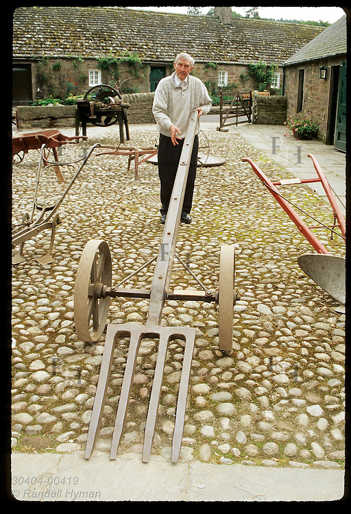 Docent at Angus Folk Museum demonstrates fork-like lever once used to move boulders in fields; Glamis, Angus, Scotland.