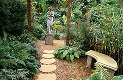 Path leading towards statue with bed of ferns and stone seat