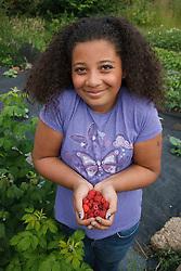 Girl with handful of raspberries