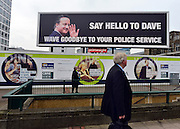 © Licensed to London News Pictures. 03/10/2012. Birmingham, UK A man walks past a billboard banner saying 'Say Hello to Dave, Wave Goodbye To YOur Police Service' opposite the entrance to The Conservative Party Conference at the ICC today 8th October 2012. Photo credit : Stephen Simpson/LNP