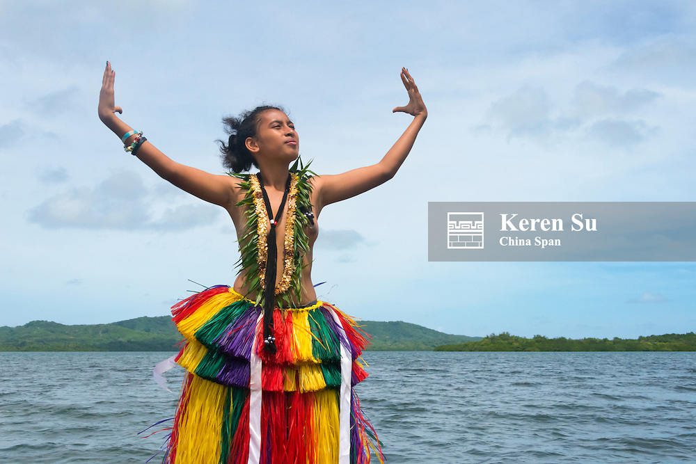 Yapese girl in grass skirt standing by the ocean, Yap Island, Federated States of Micronesia