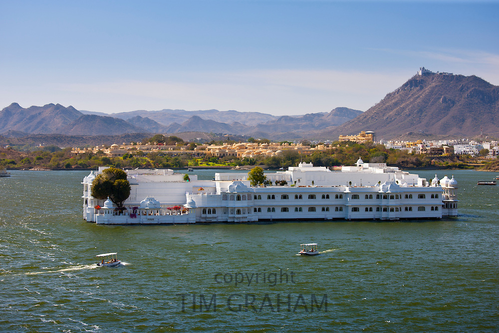 The Lake Palace Hotel, Jag Niwas, on island site on Lake Pichola with tourist boats arriving and leaving in Udaipur, Rajasthan, India