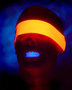 Young man gritting teeth while blindfolded with a glowing orange band.Black light