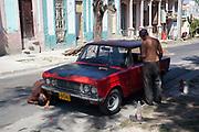 Two Cuban men fixing an old car Lada Skoda on the side of the road, Santiago de Cuba, Cuba.