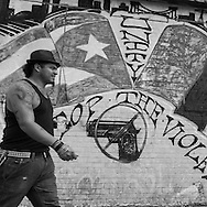 New York , Brooklyn ,  Coney island.  People passing by a memorial mural painting, against violence and guns, celebrating the death of one young citizen. Mermaid parade on Brighton beach