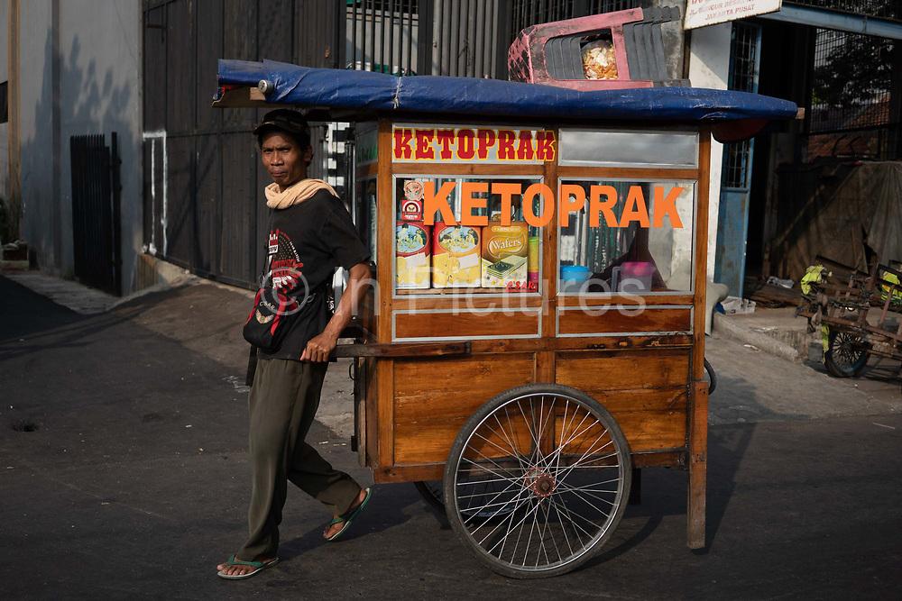 A street vendor walks along a street on 9th June 2018 in Jakarta, Java, Indonesia.