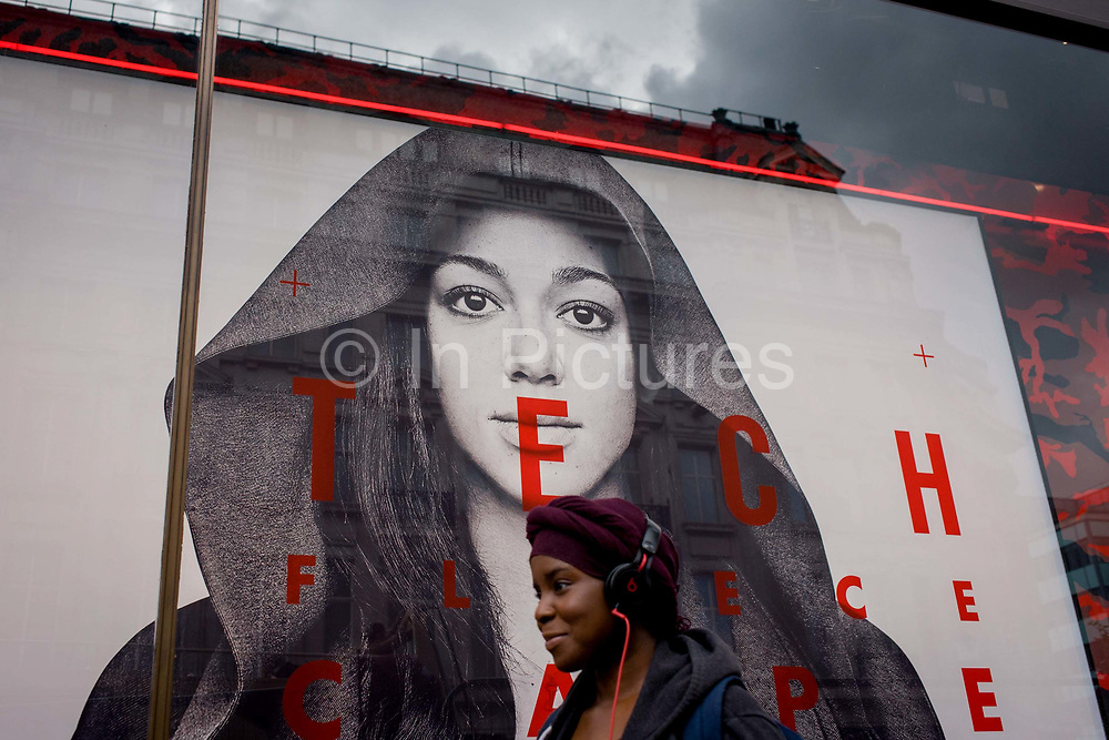 A young woman wearing headphones walks beneath a large female model's face advertising Nike's Tech Fleeces. We look from a low angle, up at the large model's face who watches us with a steady gaze from under her hood. Below her is a young woman wearing a hat and earphones, walking underneath the epitome of beauty and modern style.