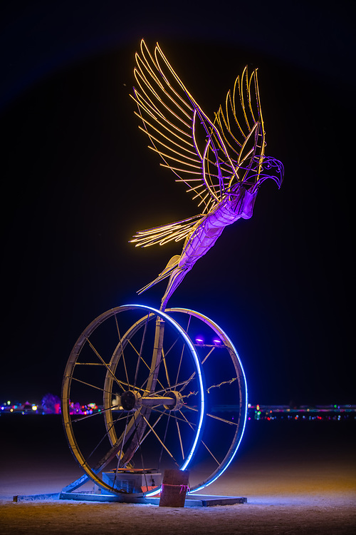 """Taking Flight<br /> by: Nicki Adani<br /> from: Mill Valley, CA<br /> year: 2019<br /> <br /> Nicki Adani's """"Taking Flight"""" emboldens visitors to be who they truly are, inspiring them to leave behind what is holding them back. A 10-foot tall feminine bird-like figure, welded from raw steel rods and tubes, her wings spread wide, takes flight from her perch upon a 10-foot tall spoked wheel, representing the circle of life. Viewers interact by making colorful ropes and weaving them into the wheel as a metaphor of releasing one's past. Experiences already lived through can't be erased, but they can speak their truths, and be let go. In the process, individuals can connect to their inner strength allowing them to spread their wings to fly free.<br /> <br /> URL: http://time2flyart.com<br /> Contact: nicki@time2flyart.com<br /> <br /> https://burningman.org/event/brc/2019-art-installations/?yyyy=&artType=H#a2I0V000001AW74UAG"""