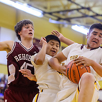 Tohatchi Cougar Rooster Yazzie (44) grabs a rebound away from teammate Bryen Chee and Rehoboth Lynx Josh Byker (45) Thursday at Tohatchi High School.