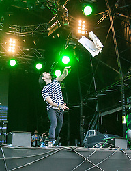 """Steve Aoki throws his cake into the crowd, playing the main stage, Saturday at Rockness 2013, the annual music festival which took place in Scotland at Clune Farm, Dores, on the banks of Loch Ness, near Inverness in the Scottish Highlands. The festival is known as """"the most beautiful festival in the world"""" ."""