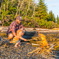 A man and his young sons enjoy a camp fire on East Gosling Island in Casco Bay, Harpswell, Maine.