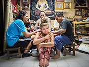 "27 MAY 2015 - BANGKOK, THAILAND:  EMILY, a visitor to Thailand from the United Kingdom, looks up while she gets a sacred Sak Yant tattoo from AJARN NENG ONNUT. Ajarn Neng is a revered master of sacred tattoos and sees people all day at his Bangkok home. Sak Yant (Thai for ""tattoos of mystical drawings"" sak=tattoo, yantra=mystical drawing) tattoos are popular throughout Thailand, Cambodia, Laos and Myanmar. The tattoos are believed to impart magical powers to the people who have them. People get the tattoos to address specific needs. For example, a business person would get a tattoo to make his business successful, and a soldier would get a tattoo to help him in battle. The tattoos are blessed by monks or people who have magical powers. Ajarn Neng, a revered tattoo master in Bangkok, uses stainless steel needles to tattoo, other tattoo masters use bamboo needles. The tattoos are growing in popularity with tourists, but Thai religious leaders try to discourage tattoo masters from giving tourists tattoos for ornamental reasons.      PHOTO BY JACK KURTZ"