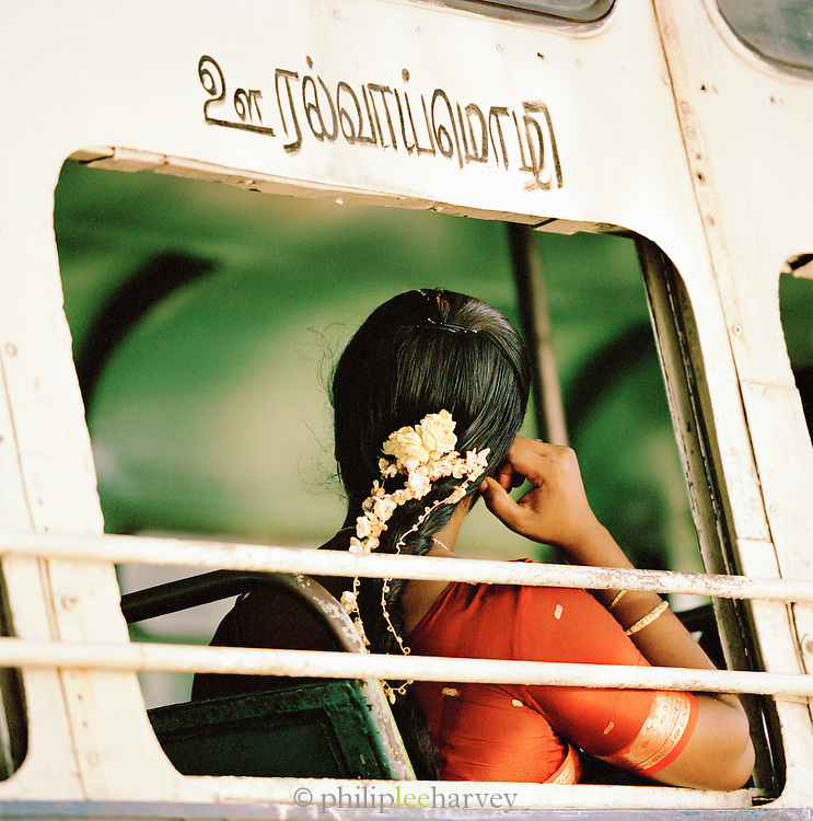 Local woman on a bus with flowers in her hair, Kerala, India.