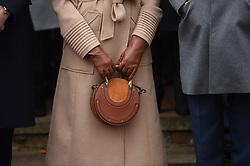 Meghan Markle holds her Chloe handbag as she leaves the Christmas Day morning church service at St Mary Magdalene Church in Sandringham, Norfolk.