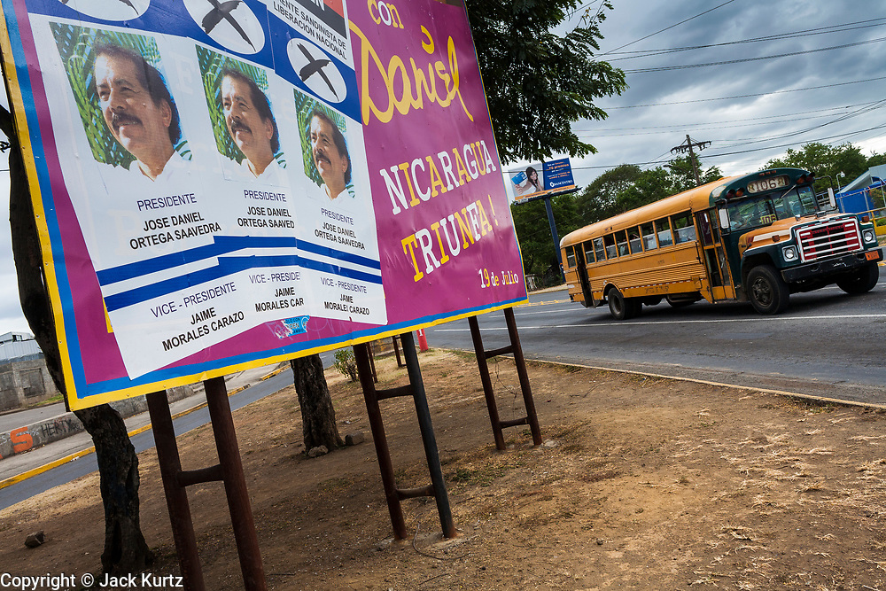 """07 JANUARY 2007 - MANAGUA, NICARAGUA: A bus passes a campaign poster for Daniel Ortega and the Sandanista party in Managua, Nicaragua. The Sandanistas won the November election and took power in January, 17 years after they were swept from power by the UNO opposition coalition headed by Violetta Chamorro. The Sandanistas ruled Nicaragua from 1979 to 1990 after they defeated the Somoza government. Their tenure was marked by advances in education and health care, but also by a war against the """"Contras"""" an anti-Sandanista army organized and funded by the Reagan administration.  Photo by Jack Kurtz"""