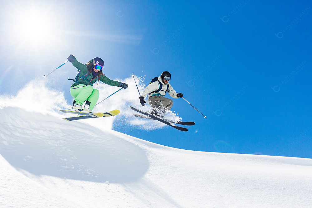 Young woman and man skiing and jumping in powder snow