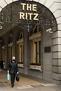 People wearing face masks pass the iconic sign for the Ritz Hotel on 25th May 2021 in London, United Kingdom. As the coronavirus lockdown continues its process of easing restrictions, more and more people are coming to the West End as more businesses open.