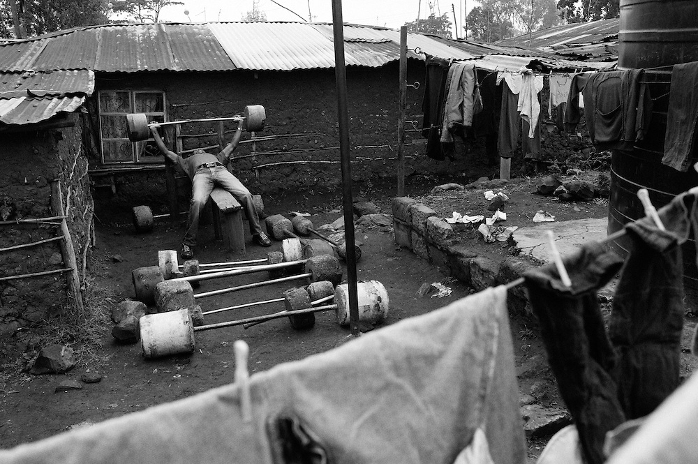 """NAIROBI, KENYA - AUGUST 15, 2011: Kamau """"Kelly"""" Nganga trains with handmade cement weights in Kibera slum. <br /> <br /> Within Kenya's progressive youth culture is the Kibera Olympic Boxing Club, a group of low-income adolescents from the slum whose leader uses boxing as a way to engage with idle youth. The group's ethnic diversity is remarkable given Kenya's 2008 post-election violence in which people from several tribes were forced violently out of slums. Together, these boxers represent a nascent trend of cross-tribe brotherhood in a healing nation."""