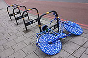 A ladies' bike covered in blue plastic wrapping tape is locked up on an empty bike stand in south London. For unknown reasons, this bike has been enveloped with this blue paper in this south London street. It leans against other vacant racks designed to park others tidily on the pavement.